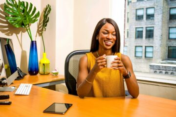 Woman sitting behind a desk top a coffee cup.